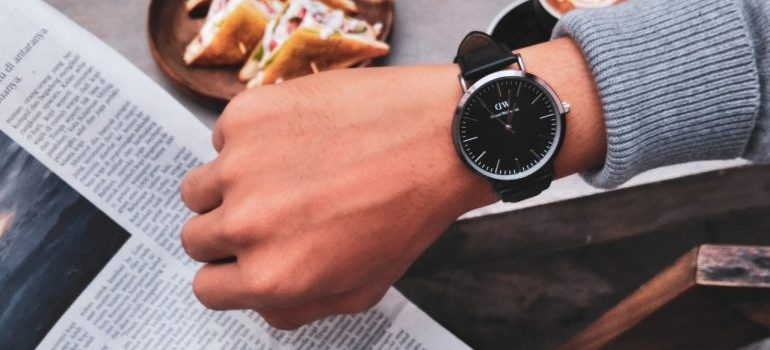 A watch, on the hand of a person reading a newspaper