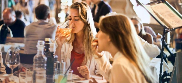 Two girls having food and drinks in the restaurant
