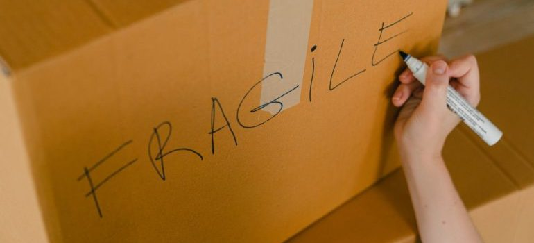 A person writting fragile on the moving box