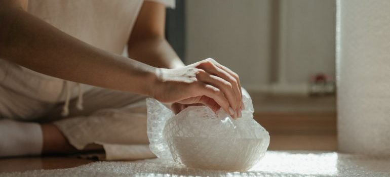 A person wrapping an item in bubble wrap as the way of how to secure when moving fragile items to Fairfax County